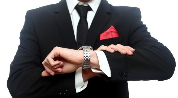 Person i kostym som tittar på sitt armbandsur