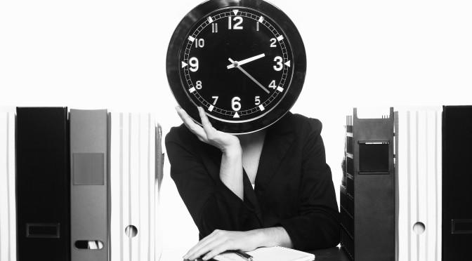 Bild på en kvinna vid ett skrivbord fullt med papper och pärmar som håller en klocka framför ansiktet.