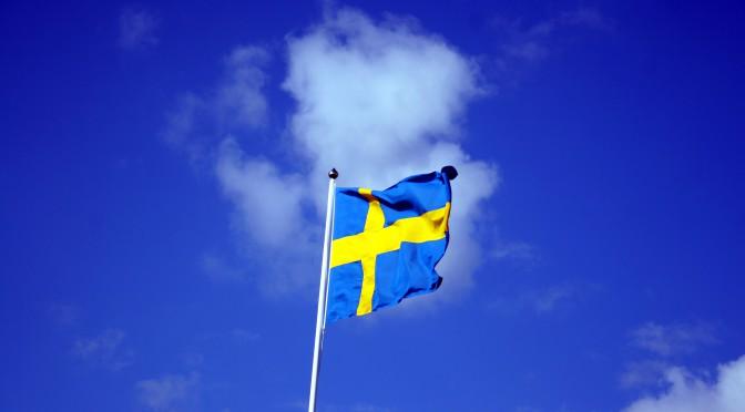 En hissad svensk flagga mot blå himmel