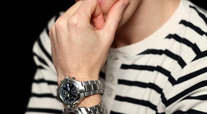 En funderande man som håller sig om hakan och har två armbandsur på sig