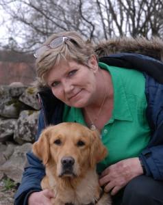 Annika Östberg sitter på knä med hennes hund Tasha, en golden retreiver.